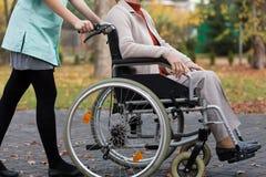 Madame sur le fauteuil roulant et l'infirmière Photographie stock