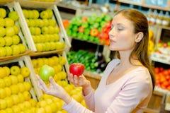 Madame tenant des pommes deux variétés différentes photos stock