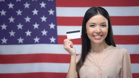Madame tenant la carte de crédit sur le fond de drapeau des Etats-Unis, opérations bancaires internationales banque de vidéos