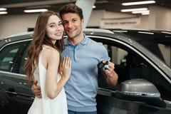 Madame tenant la voiture proche avec l'ami au concessionnaire automobile Images stock