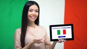 Madame tenant le comprimé avec pour apprendre l'appli italien, drapeau de l'Italie sur le fond, éducation clips vidéos