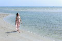 Madame Walking sur la plage photo stock