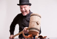 Madcap laughs with big hammer on money Royalty Free Stock Photography