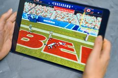Madden nfl on ipad. Bishkek, Kyrgyzstan - January 21, 2019: Girl playing a mobile game madden nfl of ea sports company on ipad pro royalty free stock photo