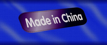 Made in China. An image showing a clothes label with Made in China written on it and stitched to a piece of fabric. For the concept of mass production of cheap Stock Photography