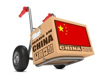 Made in China - Cardboard Box on Hand Truck. Cardboard Box with Flag of China and Made in China Slogan on Hand Truck White Background. Free Shipping Concept royalty free stock photo