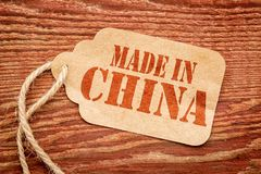 Made in China -  price tag. Made in China  sign - red stencil text on a paper price tag against grunge wood Stock Photos