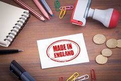Made in England stamp. Wooden office desk with stationery, money Royalty Free Stock Photos