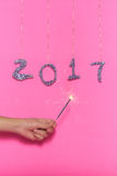 2017 made with glitter and womans hand holding a sparkle on pink Stock Images