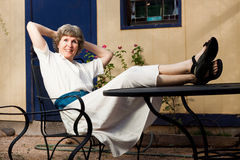 Made a good investment. Relaxed senior lady putting her feet up after a successful investment and beginning her retirement Royalty Free Stock Photos