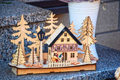 Made by hand from wood panorama of the typical winter landscape. The trees, the house behind the fence, lantern. Panorama decorate cakes. All this standing on Stock Images