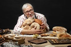 Happy old baker looking at camera and smiling while hugging loaves of bread. Made with love. Confident old grey-haired baker wearing spectacles holding freshly stock photo