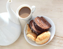 Chocolate biscuit and coffee with milk. On the made old, bleached board there is a cup of coffee, a biscuit and a croissant in a saucer Stock Photo