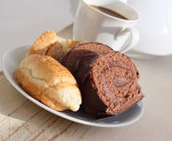 Chocolate biscuit and coffee with milk. On the made old, bleached board there is a cup of coffee, a biscuit and a croissant in a saucer Royalty Free Stock Photo