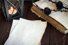 Made old sheets of paper, books and candle. On a wooden table Royalty Free Stock Photos
