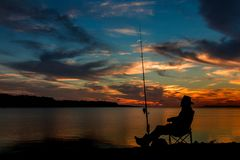 Fishing At Sunset. Made sitting by his fishing rod at sunset royalty free stock images