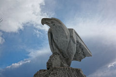 Made of stone eagle on a background of trees. Stock Image
