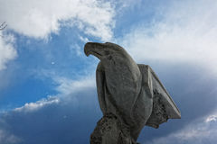 Made of stone eagle on a background of trees. Royalty Free Stock Image