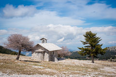 Made of stones chapel. Winter landscape with a small chapel, trees and blue sky with clouds  on mountain Helmos near Kalavryta town in Greece Stock Photo