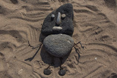 Made from stones. Little man with stones on the sand Stock Photography