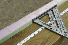 Made to Measure. Diagonal view of a section of a tape measure and speed square on a two by four Stock Images