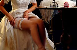 Made-to-measure per bespoke tailoring bridal gown. Garter with ruche edgingr. Sewing workshop per bespoke tailoring bridal gown. Woman trying on wedding dress stock photo