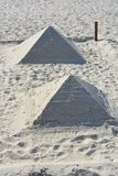 Made two pyramids of white sand and sea shells on the Black Sea beach during the day royalty free stock photos