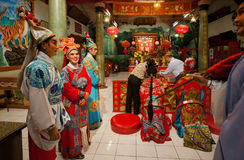 Made-up actores of Chinese opera in vintage costumes praying inside colorful Buddhist temple in old style Royalty Free Stock Image
