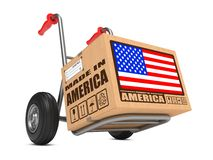 Made in USA - Cardboard Box on Hand Truck. Cardboard Box with Flag of USA and Made in America Slogan on Hand Truck White Background. Free Shipping Concept stock photo