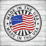 Made in the USA. Stamp on wooden background. Vector stamp with flag of The USA, circular lettering made in the USA on wooden background Stock Image