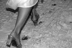 Made for Walking. A bride in heels walking through dirty snow royalty free stock image