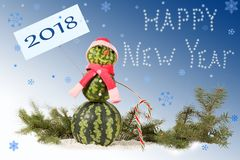 Made from watermelon Snowman in red hat and scarf with candy cane on blue background and falling snowflakes. Stock Image