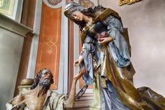 A madeira cinzelou a estátua de Saint Elizabeth com mendigo em uma caridade g fotos de stock