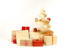 A madeira da árvore de Natal com as caixas de presente de época natalícia decoradas com fita e letra a Santa Claus isolou-se no f Imagem de Stock