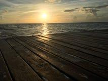 Madeira da doca da água do mar do nascer do sol imagens de stock royalty free