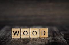 A madeira da palavra é feita de cubos de madeira brilhantes com letras pretas sobre Fotos de Stock
