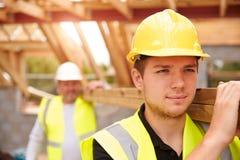 Madeira de And Apprentice Carrying do construtor no canteiro de obras foto de stock royalty free