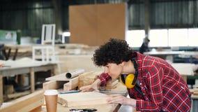Madeira de lustro do operário da jovem senhora com o bloco abrasivo que trabalha na sala de trabalho video estoque