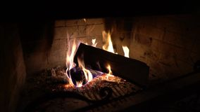 Madeira de queimadura na chaminé tradicional na obscuridade filme