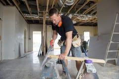 A madeira de trabalho atrativa e segura do corte do homem do carpinteiro ou do construtor do construtor com manual viu no trabalh fotografia de stock royalty free