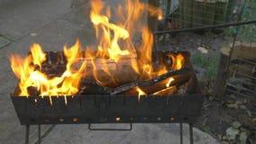 Madeira e carvão ardentes no soldador Preparando o no espeto e a grade do assado video estoque