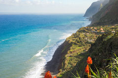 Madeira Island coastline with cliffs, village and blue ocean. Beutiful romantic view on Madeira Island coastline - high cliffs, small village, rocks, beach, red Royalty Free Stock Photos