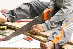 Madeira masculina do sawing do carpinteiro No lugar de trabalho Ferramenta do artesão do fundo Fotos de Stock Royalty Free