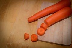 A madeira pôs sobre cenouras grandes na cozinha Foto de Stock Royalty Free