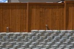 Madeira que cerca na parede de retenção de pedra da pilha do cimento Fotos de Stock Royalty Free
