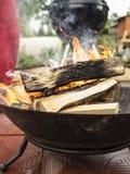 Madeira que queima-se na bacia da fogueira para preparar os carvões para a grade imagens de stock royalty free