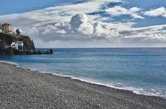 Madeira`s empty stone beaches in autumn. Walking an empty stone beach in fall. It`s a sunny day with clouds heading to the island Royalty Free Stock Images