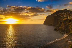 Madeira Sunset. Camera de Lobos, beach scene and town on clifftop Stock Photo