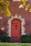 A madeira vermelha arqueou a porta cercada por um quadro da rocha em uma casa do tijolo com o castelo como o hardware com as folh foto de stock royalty free