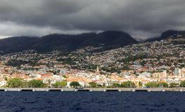 Madeira view from the sea. Beautiful cityscape view of the city Funchal, Madeira, seen from the Atlantic ocean, with ominous clouds royalty free stock photo